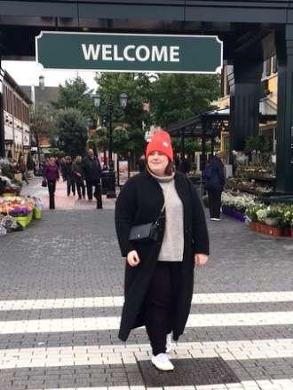 Schwarzer Mantel, orangene Mütze und Oversized Pullover